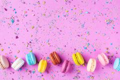 Colorful dessert macaron or macaroon on pink punchy background top view. Flat lay stock image