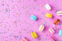 Colorful dessert macaron or macaroon on pink punchy background top view. Flat lay style stock photo