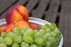 Peaches and grape bunch on a garden table royalty free stock photography