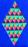 Colorful diamond shape. An illustration of a diamond shape with colorful triangles inside on a blue background Royalty Free Stock Images