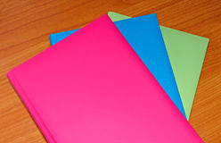 Colorful diaries. Three colorful diaries on a wooden table Stock Image