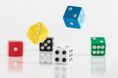 Colorful dice falling on the table stock photography