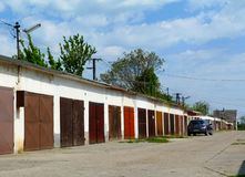 Colorful different garage doors in diminishing perspective. Colorful varying and distinct wooden and steel garage doors in diminishing perspective along an alley royalty free stock photos