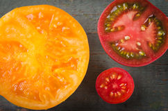 Colorful different kinds of tomatoes on wooden background Royalty Free Stock Photo