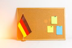 Colorful different stickers pined on the corkboard and German flag staying on wooden white table, horizontal.  Royalty Free Stock Photos