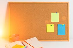 Colorful different stickers pined on the corkboard with notepad and coffe on white wooden table, horizontal. Planning concept. Ton. Colorful different stickers Royalty Free Stock Photo