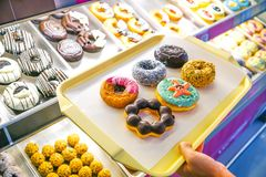 Colorful and different type of donuts. Customer choosing colorful and different type of donuts from shelves royalty free stock photo
