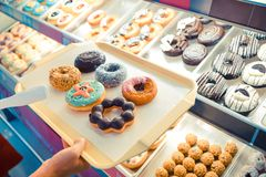 Colorful and different type of donuts. Customer choosing colorful and different type of donuts from shelves stock photo