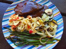 Colorful dinner plate with grilled steak & veggies. Colorful dinner plate with grilled steak, asparagus, onions, zucchini and pasta royalty free stock photography