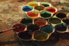 Colorful dirty artistic table with color palettes and paint brushes SELECTIVE FOCUS Royalty Free Stock Image