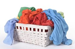 Colorful dirty clothes in laundry basket. Isolated over white background stock photo
