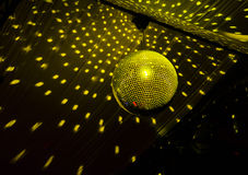 Colorful disco ball in a nightclub. Colorful turquoise blue mirrored metallic disco ball in a nightclub hanging in the darkness with copyspace Stock Images