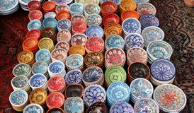 Colorful dishes of stylish Tunisian artisanal ceramics, on the carpet of a market. Colorful dishes of stylish Tunisian artisanal ceramics, on the carpet of a Royalty Free Stock Images
