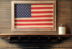Colorful display of framed flag hanging above wood shelf at fireplace. Bright and colorful image of framed weathered flag hanging above wood shelf over fireplace royalty free stock image