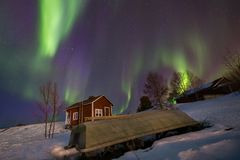 Colorful display of northern lights over a cabin and boat in Inari, Finland stock image