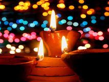 Colorful Diwali. Traditional lamps lit in front of colorful lighting, during Diwali festival in India