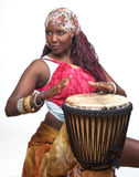 Colorful Djembe Drummer. A festive african woman dressed in colorful clothing plays the djembe drum Royalty Free Stock Image