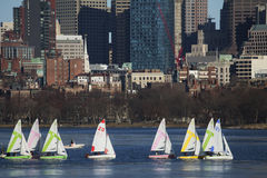 Colorful docked sailboats and Boston Skyline in winter on half frozen Charles River, Massachusetts, USA Royalty Free Stock Image