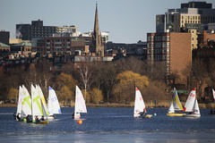 Colorful docked sailboats and Boston Skyline in winter on half frozen Charles River, Massachusetts, USA Stock Photo