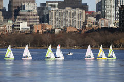 Colorful docked sailboats and Boston Skyline in winter on half frozen Charles River, Massachusetts, USA Stock Photos
