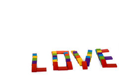 Colorful dominos write love. Colorful wooden dominos write the word love on a white background Stock Photography