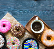 Colorful Donuts breakfast composition with different color styles. Of doughnuts and fresh coffee on the side over an aged wooden desk background stock photos
