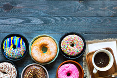 Colorful Donuts breakfast composition with different color styles. Of doughnuts and fresh coffee on the side over an aged wooden desk background stock photography