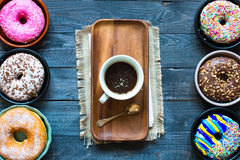 Colorful Donuts breakfast composition with different color styles. Of doughnuts and fresh coffee on the side over an aged wooden desk background royalty free stock image