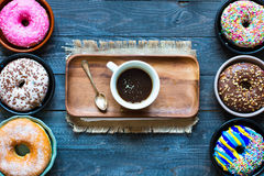 Colorful Donuts breakfast composition with different color styles. Of doughnuts and fresh coffee on the side over an aged wooden desk background royalty free stock images
