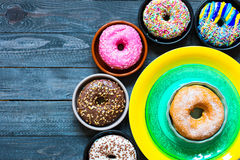 Colorful Donuts breakfast composition with different color styles. Of doughnuts over an aged wooden desk background stock photos