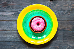 Colorful Donuts breakfast composition with different color styles. Of doughnuts over an aged wooden desk background stock image