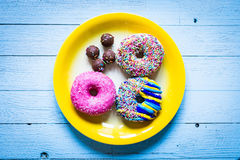 Colorful Donuts breakfast composition with different color styles. Of doughnuts over an aged wooden desk background royalty free stock photography