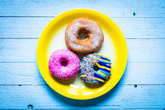 Colorful Donuts breakfast composition with different color styles. Of doughnuts over an aged wooden desk background royalty free stock image