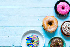 Colorful Donuts breakfast composition with different color styles. Of doughnuts over an aged wooden desk background royalty free stock images