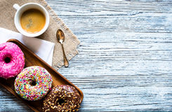 Colorful Donuts breakfast composition with different color styles. Of doughnuts over an aged wooden desk background stock photography