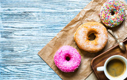 Colorful Donuts breakfast composition with different color styles. Of doughnuts over an aged wooden desk background royalty free stock photo