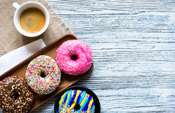 Colorful Donuts breakfast composition with different color styles. Of doughnuts over an aged wooden desk background royalty free stock photos