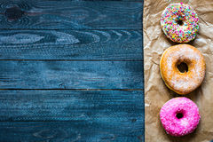 Colorful Donuts breakfast composition with different color styles. Of doughnuts over an aged wooden desk background stock images