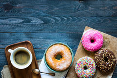 Colorful Donuts and coffee breakfast composition with different color styles. Of doughnuts over an aged wooden desk background royalty free stock images