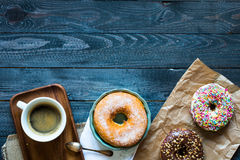 Colorful Donuts and coffee breakfast composition with different color styles. Of doughnuts over an aged wooden desk background royalty free stock photo