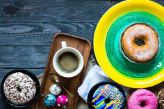 Colorful Donuts and coffee breakfast composition with different color styles. Of doughnuts over an aged wooden desk background royalty free stock image