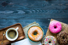 Colorful Donuts and coffee breakfast composition with different color styles. Of doughnuts over an aged wooden desk background stock photo