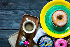 Colorful Donuts and coffee breakfast composition with different color styles. Of doughnuts over an aged wooden desk background stock images