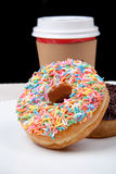 Colorful Donuts and coffee in white plate with black background. Picture of Colorful Donuts and coffee in white plate with black background Royalty Free Stock Photos