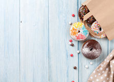 Colorful donuts in paper bag Stock Photos