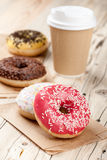 Colorful donuts and paper cup on wooden table Stock Image