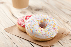 Colorful donuts and paper cup on wooden table Stock Photo