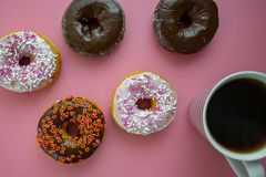 Colorful donuts on a pink table being served for breakfast with piping hot coffee. stock image