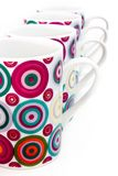 Colorful dotted mugs 3. Ceramic colorful polka-dotted white breakable drinking mugs stock photo