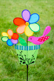 Colorful double pinwheel with bird on green grass Royalty Free Stock Images